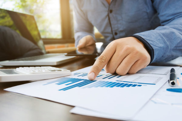 auditor or financial inspector working on sales performance report at modern workplace
